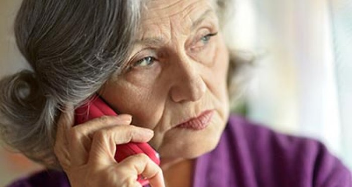 Senior on the phone with worried expression