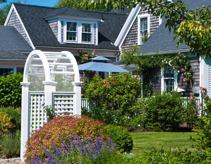 Cape Cod house with arbor, patio, umbrella and flowers