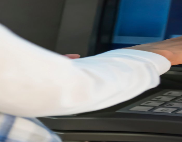 Customer inserting card into ATM machine